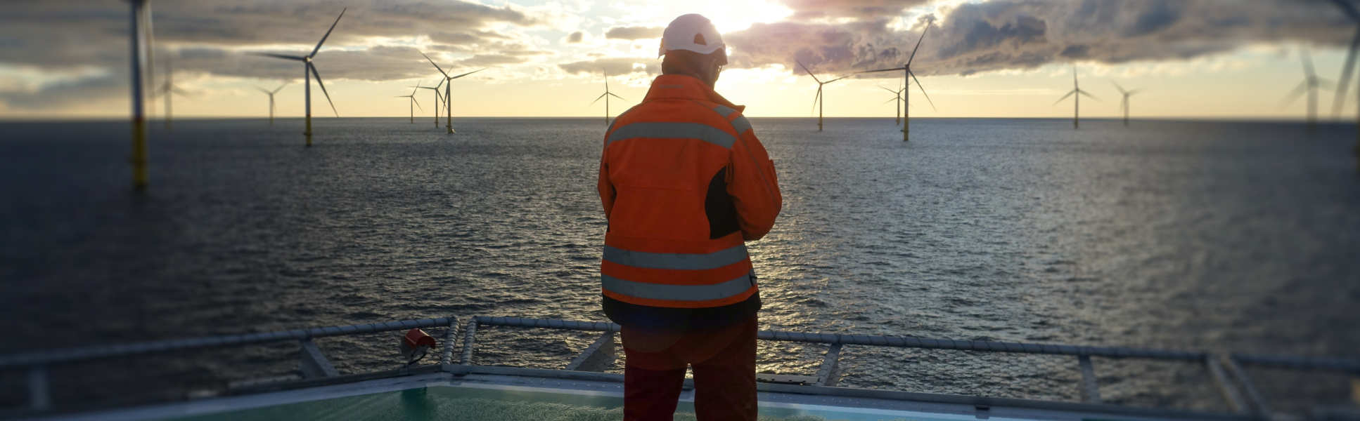 Man on a platform at sea looking out at offshore wind turbines