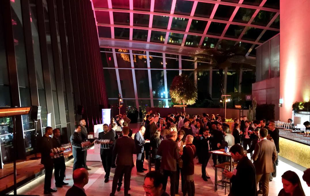 Alumni and guests mingle in front of huge windows overlooking the London skyline at night