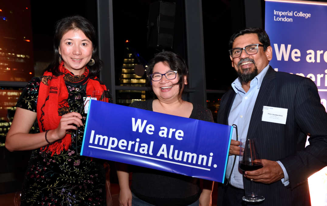 Three alumni smile at the camera in front of a view of the London skyline