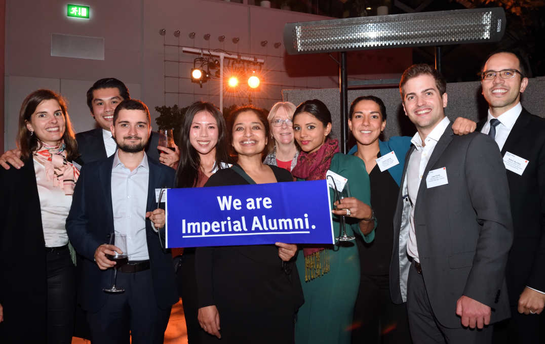 A group of alumni smiling at the camera, holding a banner that reads 'We are Imperial alumni'