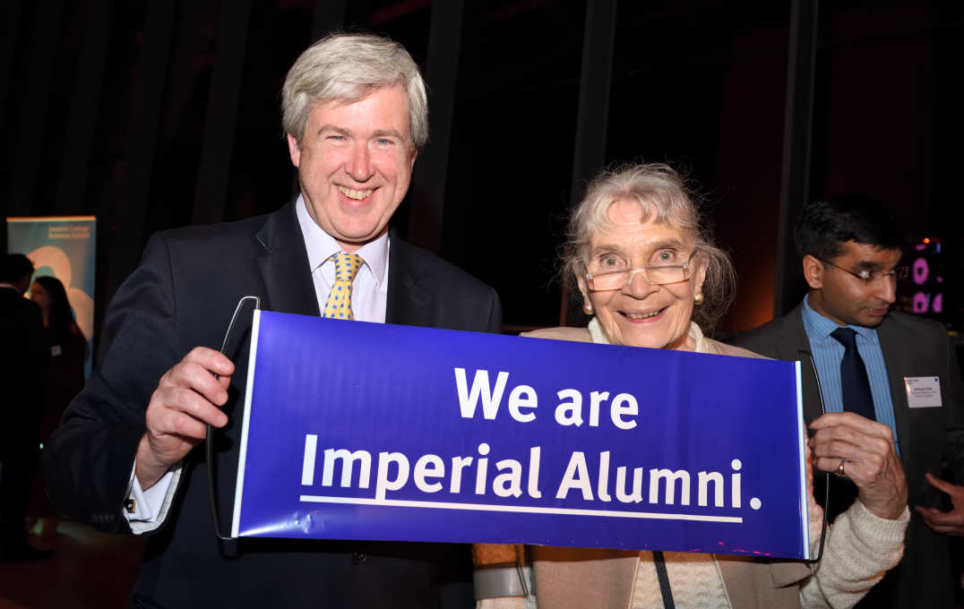 Alumni holding an Imperial banner
