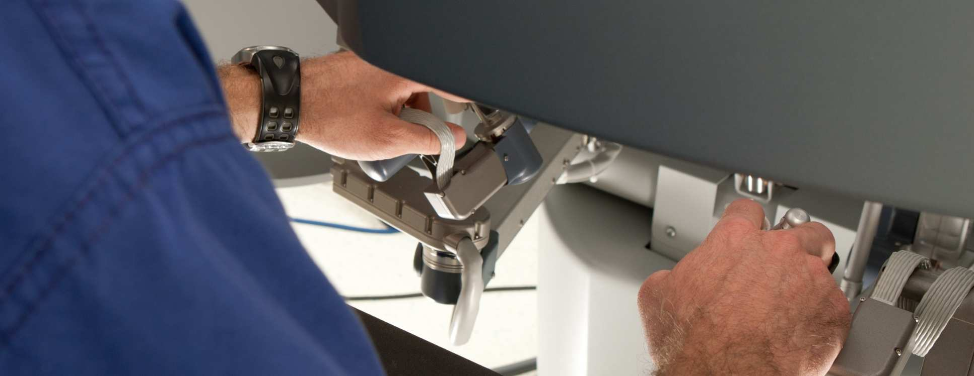 Hands operating a robotic surgery machine.