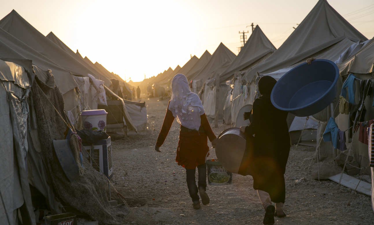 Refugee women carry supplies in a camp