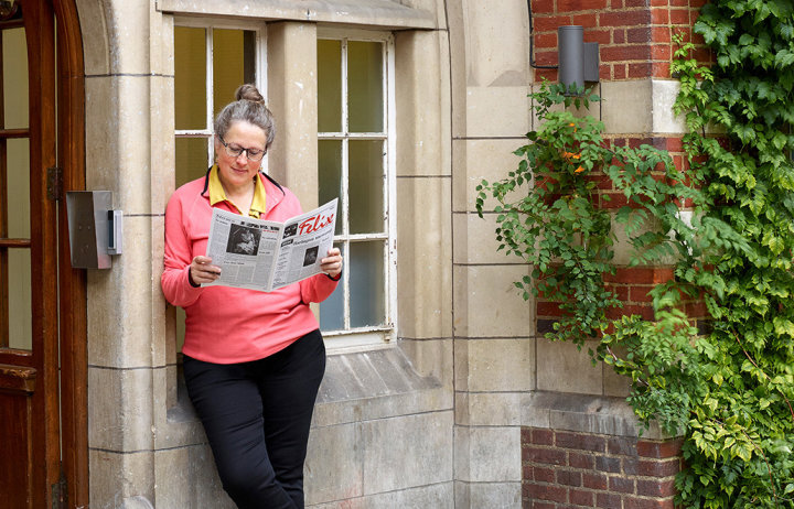 Former editor of Felix Judith Hackney reading an archive copy of the paper outside the main building at Beit Quad