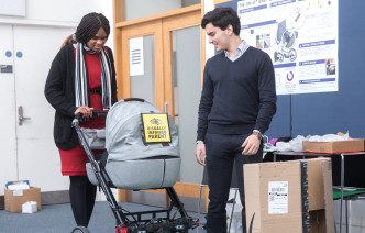 The inventor and creator of the Smart Baby Buggy stand next to their prototype