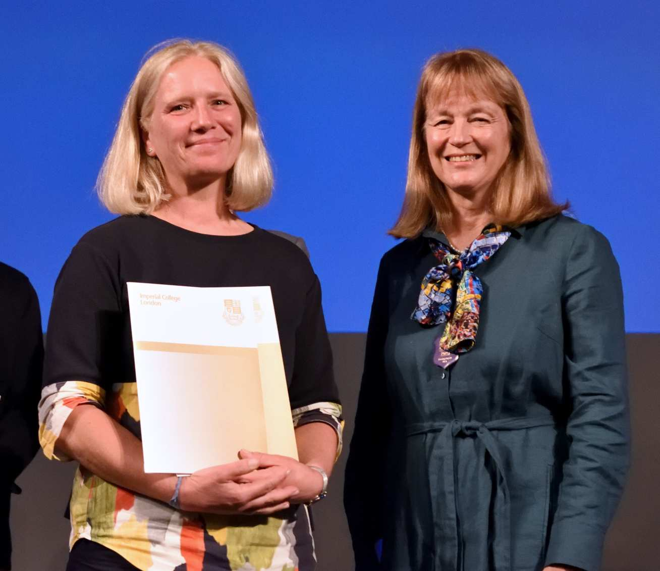 women holding certificate in hand smiling