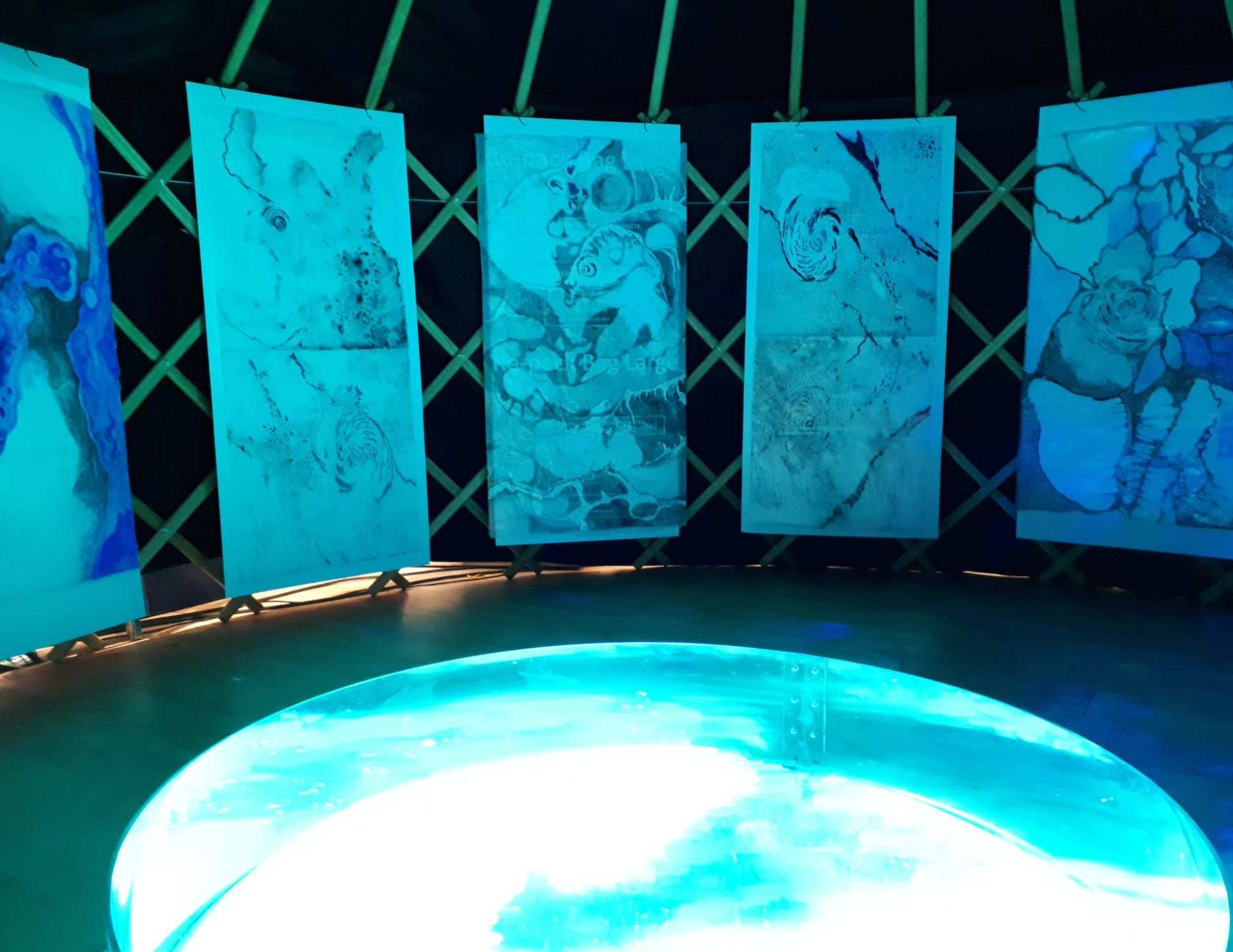 Five abstract watercolour paintings hang above a small pool of water, both are illuminated with blue light