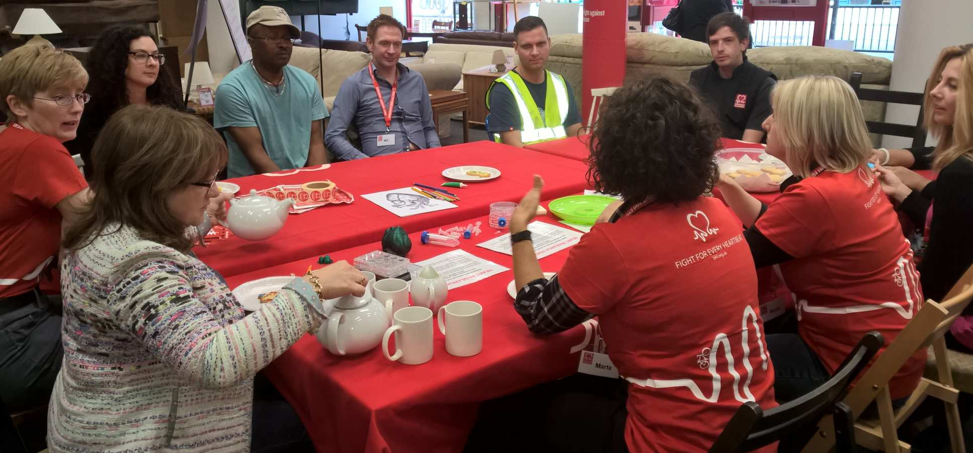 researchers & public sit round table in BHF shop