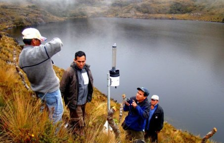 scientists with equipment to monitor water at the side of a lake in mountainous-looking country