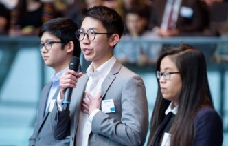 Students behind the 'Yoo-Go' start up stand by a microphone, pitching their concept at the final in City Hall