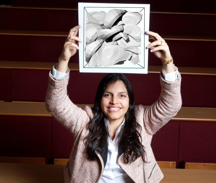 Dr Adriana Paluszny holding Image of rock fracturing planes above her head