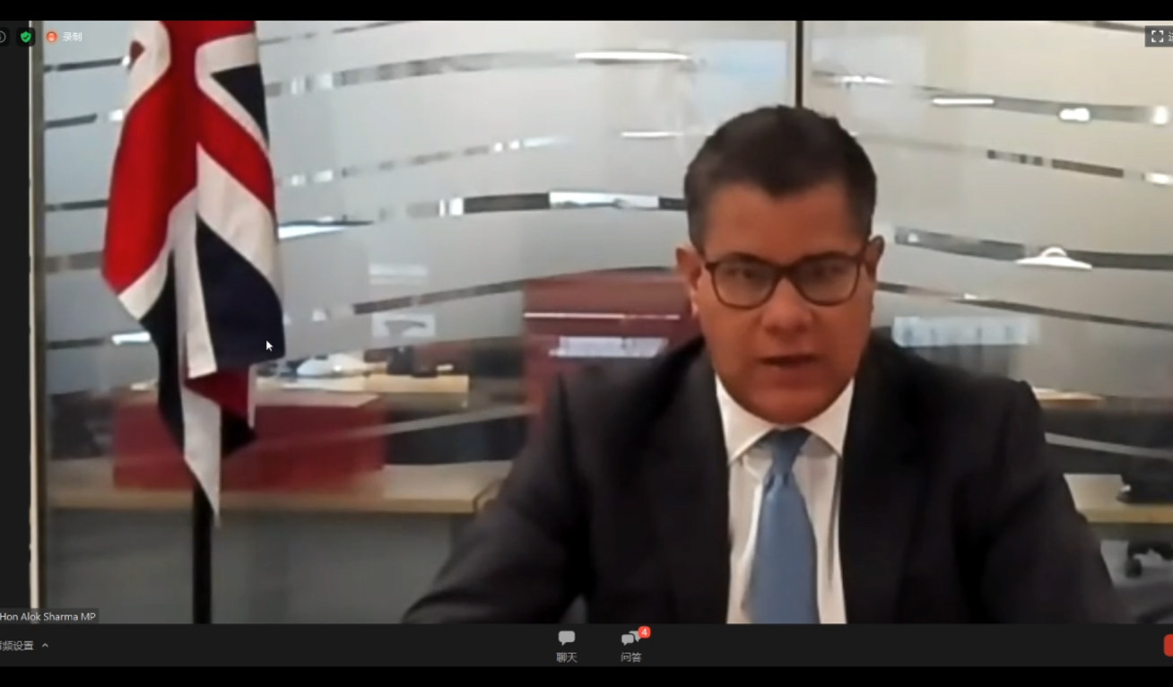 Alok Sharma viewed on a video chat screen, he sits at an office desk wearing a suit. A union flag hangs in the background.