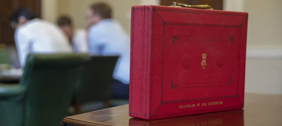 Chancellor of the Exchequer red box on a wooden table with people at a meeting table in the background.