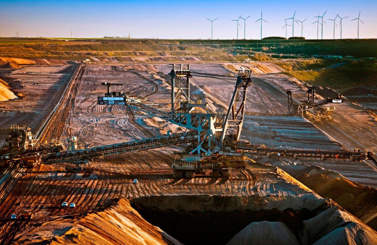Penambangan permukaan batubara coklat dengan stacker, turbin angin di latar belakang