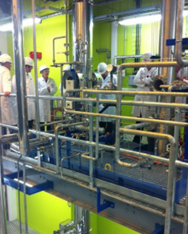 People in hard hats and lab coats in the carbon capture pilot plant