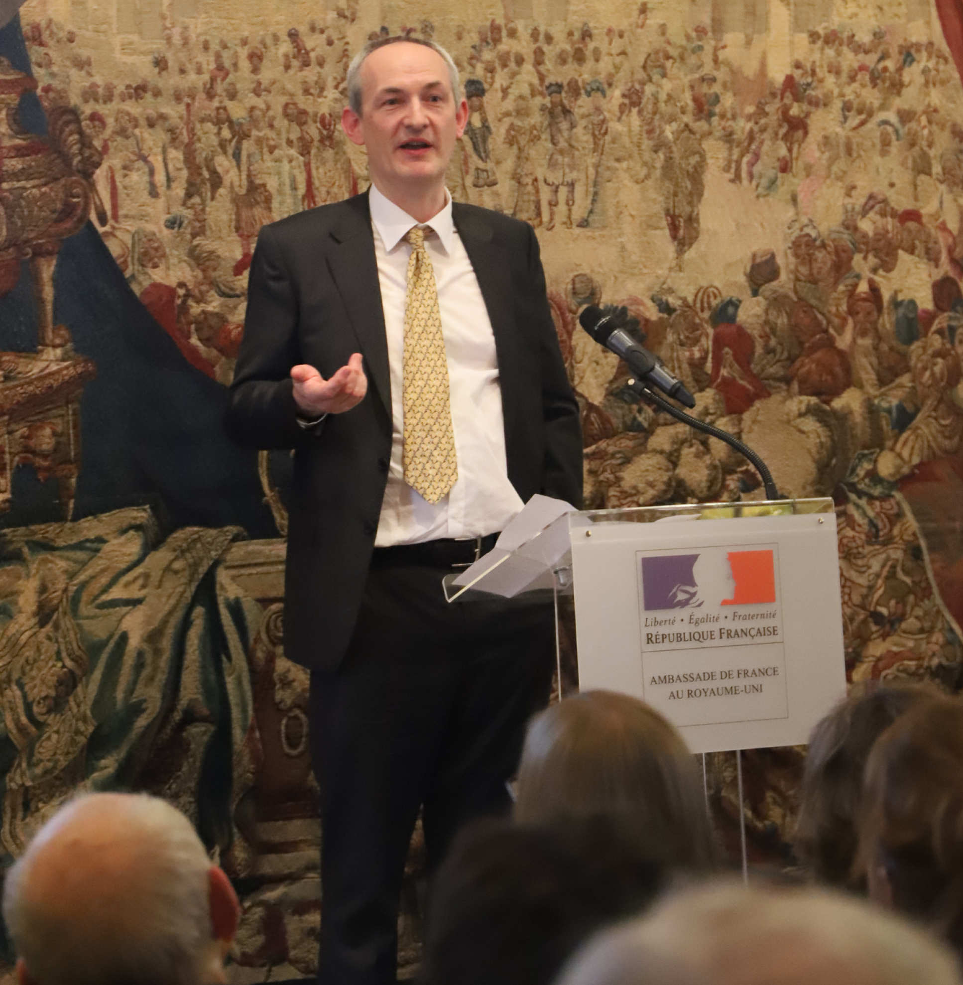 man in suit talking at lectern with tapestry in background