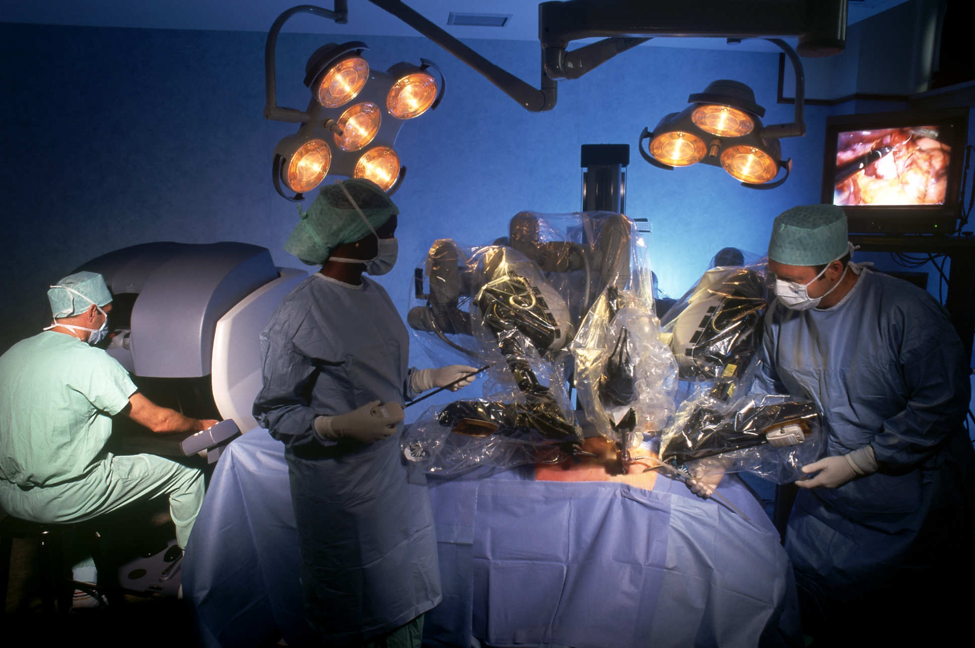Robot arms over a patient in surgery