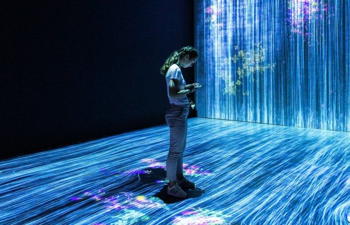 Woman standing in immersive artistic representation of data