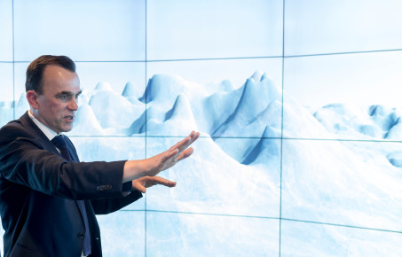 Data visualisation showing the antarctic, with Martin Siegert gesturing as he talks about it