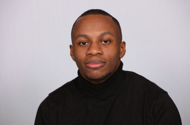 Portrait of De-Shaine Murray. De-Shaine is sat in front of a white backdrop wearing a black turtle neck