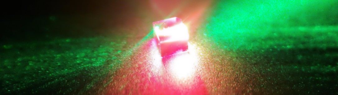 A diamond containing nitrogen-vacancy (NV) defects centres is illuminated by a 532-nm green laser.  The red light because the NV centres fluoresce. Credit: Jonathan Breeze, Imperial College London