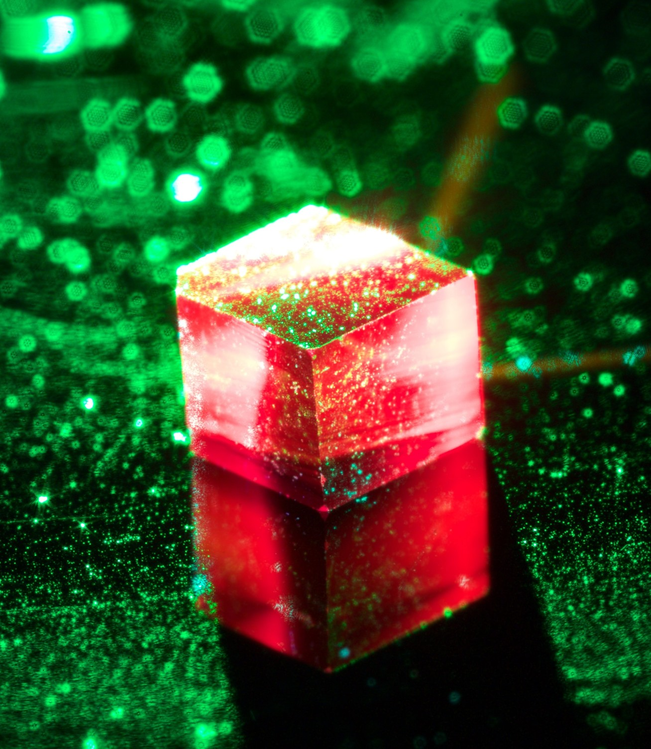 Photo of maser up close. The diamond is held inside a sapphire ring and illuminated by 532-nm green laser.  The red light is fluorescence from the NV centres.