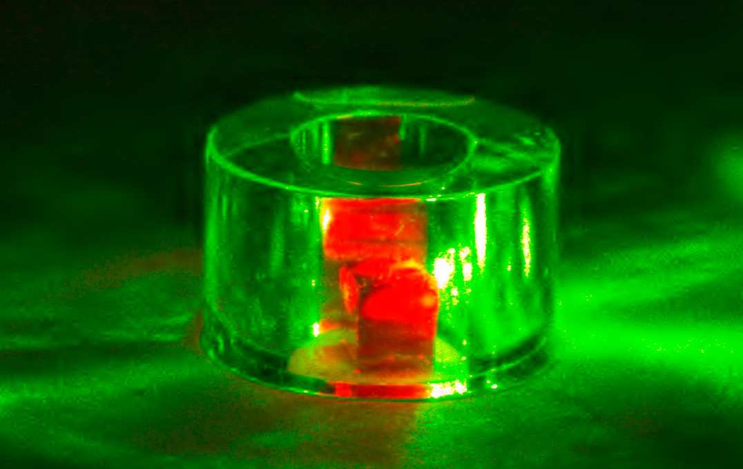 The diamond is held inside a sapphire ring and illuminated by green laser light. The red light is fluorescence from the NV centres.
