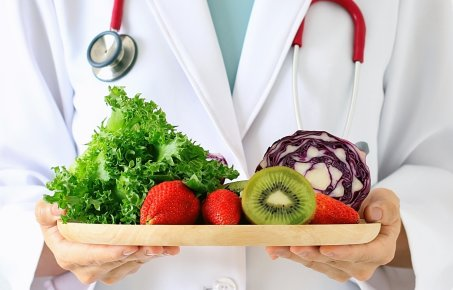 A doctor holding fruit and vegetables