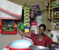 African woman in a shop in Rwanda clicking a power switch