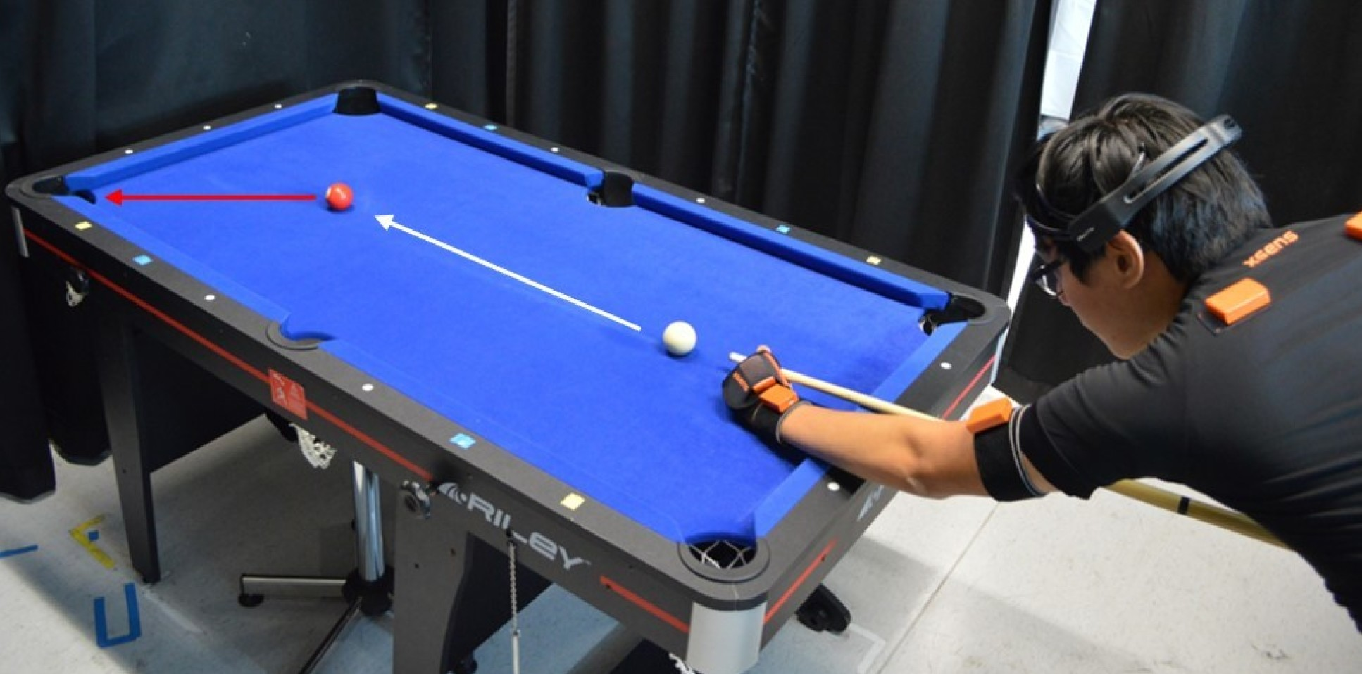 A study participant wearing motion sensors playing pool.