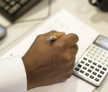 man's hand with pen and calculator