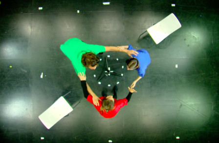 Aerial view of three people linking arms taking part in an immersive performance
