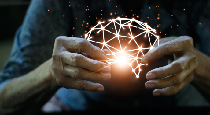 Older person's hands holding a sphere of connected lines, illuminated in the centre, to look a little bit like a brain