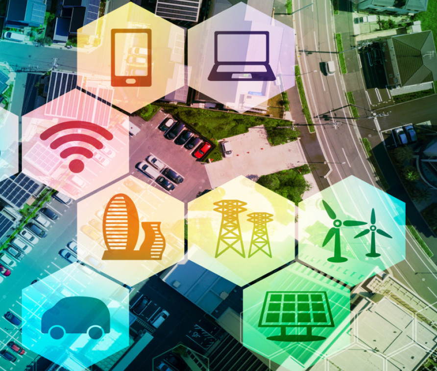 Image of bird's-eye view of a neighbourhood, with superimposed images in brightly coloured hexagons: Wi-Fi symbol, tablet, laptop, skyscrapers, electricity towers, windmills, car, solar panel.