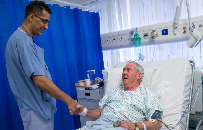 A doctor talks with his patient who has recently undergone heart surgery in the Cardiac unit