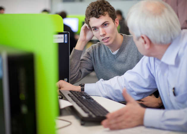 Student and tutor in conversation at a computer