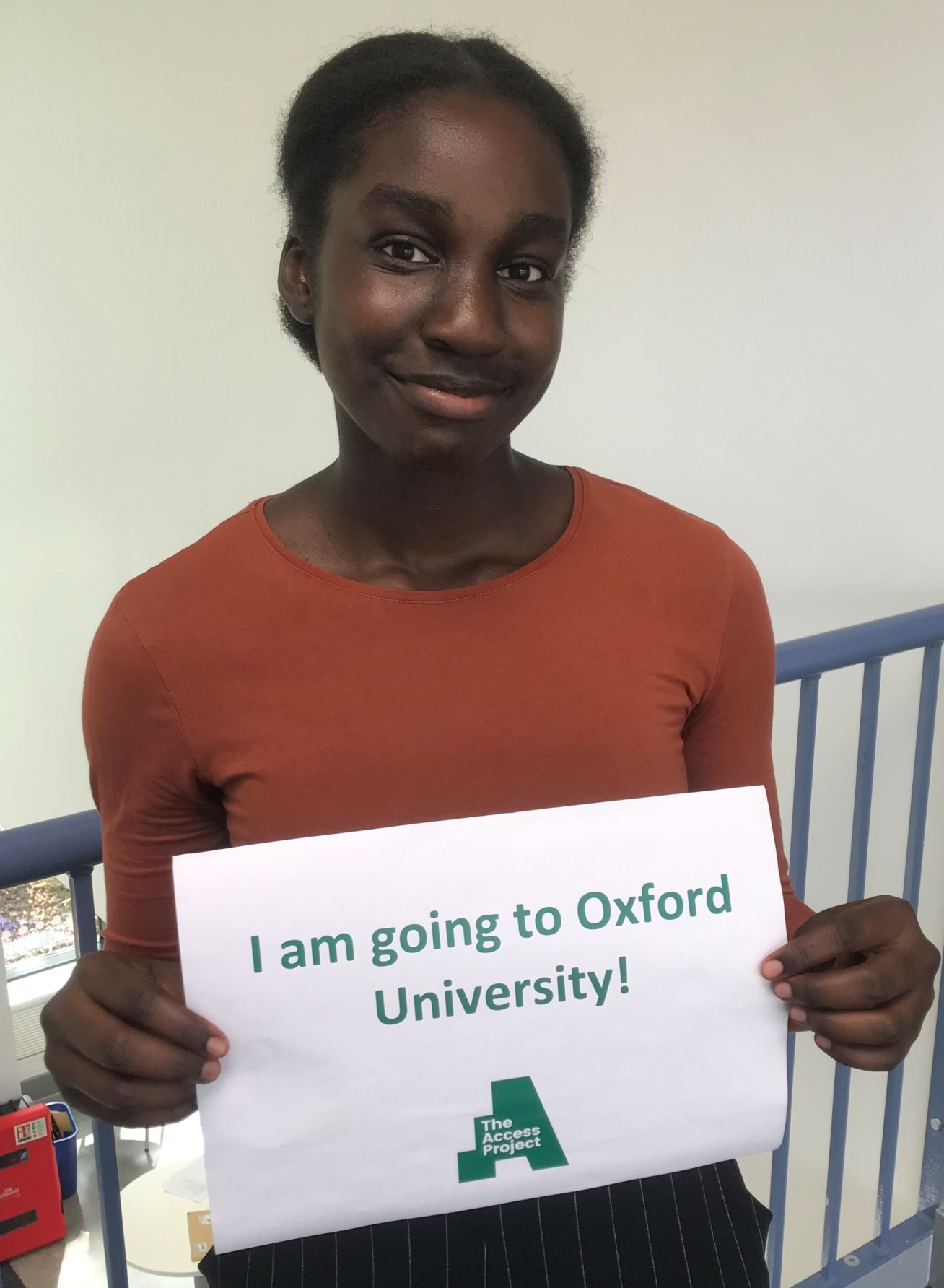 Girl holding a sign that says: 'I am going to Oxford University!'