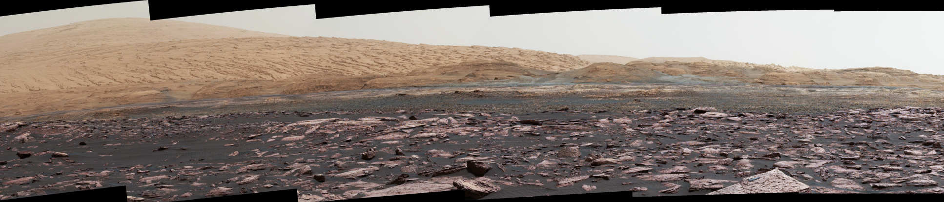 Photo taken by the Curiosity Rover on Mars showing a rocky, mountainous landscape.
