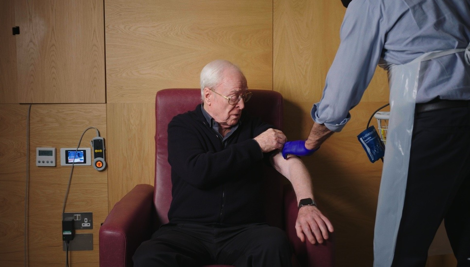 Sir Michael Caine bearing his arm with a health worker