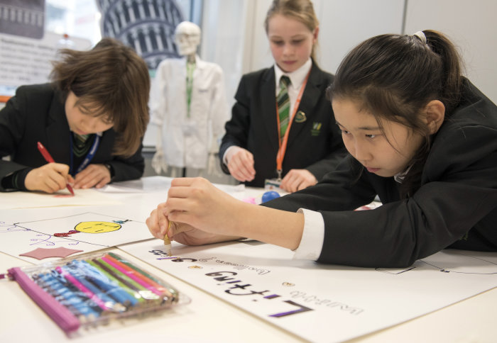 Three pupils work on a poster together