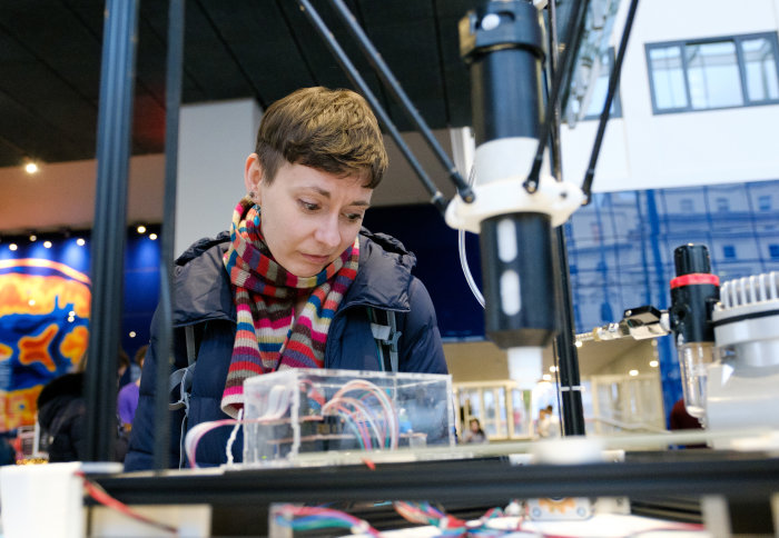Woman looking into a machine of glass and fibres
