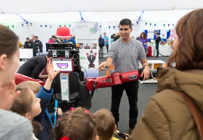 Man shows red robot to young children