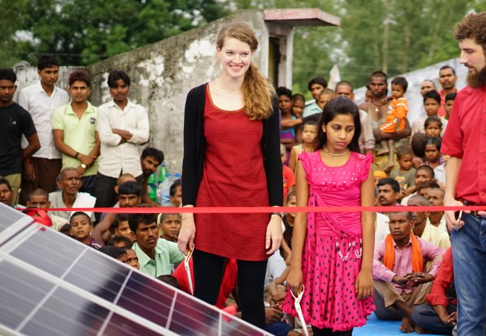 Woman and girl standing in front of solar panels