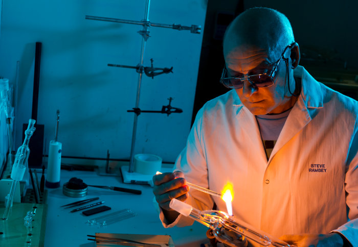 Man holding a small glass tube over a flame in a lab