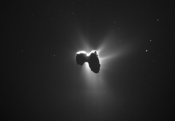 The comet on its side, its atmosphere lit from behind by the sun