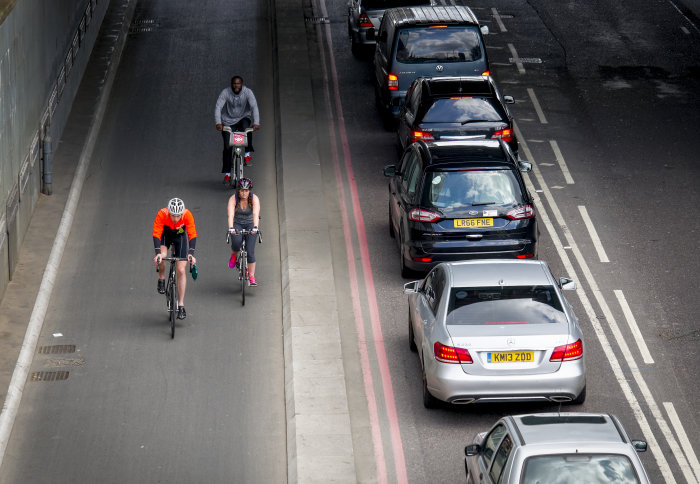 Three cyclists riding next to a line of cars stuck in traffic