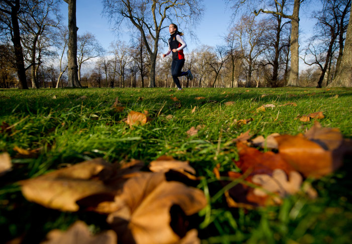 A woman running through Hyde Park on an autumn morning