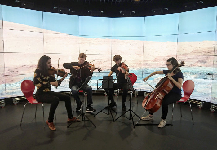 Photo of the Ligeti Quartet practising in Imperial's Data Observatory. A photo taken by the Curiosity Rover is displayed in the background.