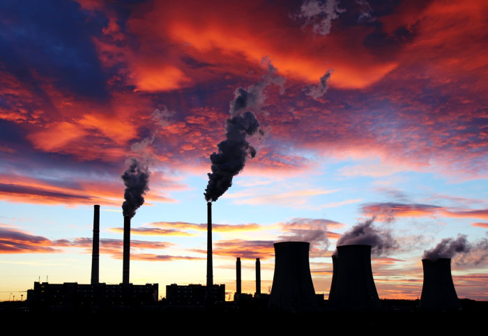 Factory pipes with smoke rising from chimneys against sunset sky