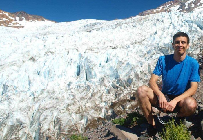 Dr Ceppi crounched down next to Coleman Glacier on Mount Baker in Washington State.